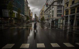 Señora cruza paso peatonal en una Gran Vía desolada durante el confinamiento